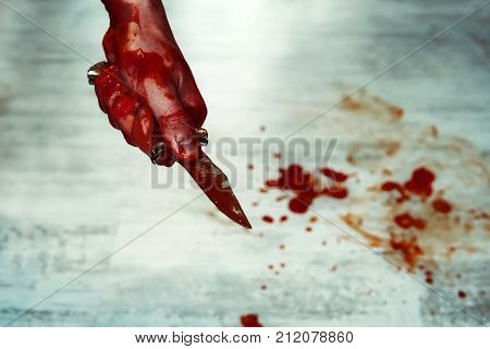 Male Hand With Bloody Knife Over Concrete Wall