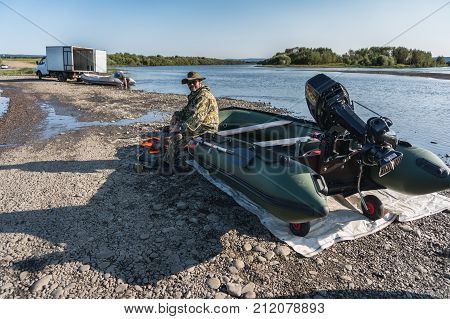 the fisherman sits in a boat with a motor on the river bank