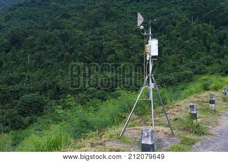 Antenna Meteorological weather station with meteorology sensors pale overcast cloudy sky and forest in background. Weather station for background. poster