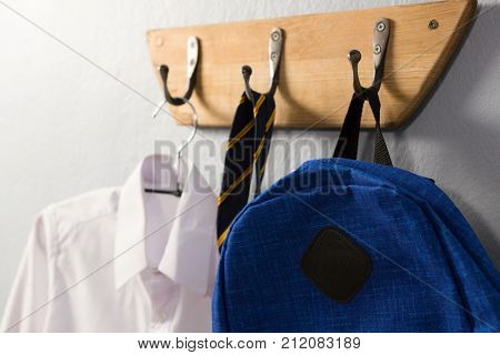 Close-up of school uniform and schoolbag hanging on hook