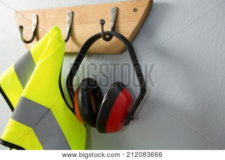 Protective workwear and earmuffs hanging on hook against grey background