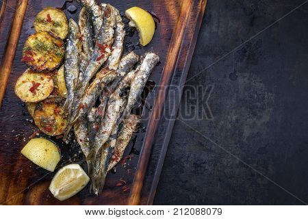 Traditional Spanish barbecue sardine with fries as top view on a cutting board with copy space right