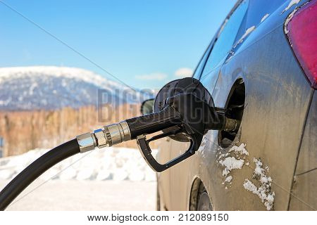 Pistol gas station in the tank of the car. Travel by car. Refueling with gasoline in the mountains. Travel by car.