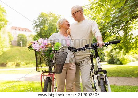 old age, people and lifestyle concept - happy senior couple with bicycles talking at summer city park
