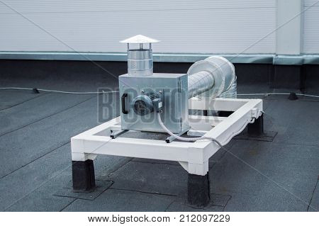 Gray centrifugal fan with ductwork on the roof