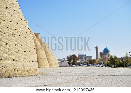 Ancient fortess brick wall against mosque, Bukhara Uzbekistan