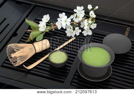 Japanese green matcha tea with powder and health drink in cup with whisk, stick stirrer and spring cherry blossom on black tray.
