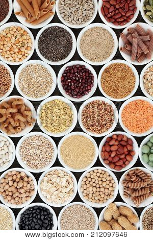 Healthy macrobiotic super food with legumes, seeds, nuts, grains, cereals and whole wheat pasta with super foods high in protein, omega 3, anthocyanins, antioxidants, minerals and vitamins, top view.