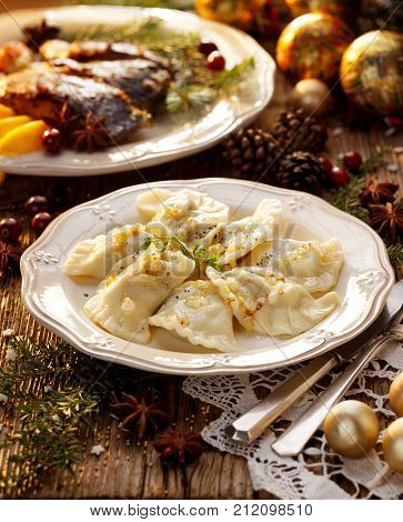 Christmas dumplings stuffed with mushroom and cabbage on a white plate. Traditional Cristmas eve dish in Poland