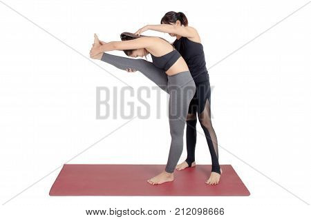 asian woman doing yoga training in Dandayamana Janushirasana or Standing Head to Knee pose with trainer teacher assists to make yoga pose isolated on white background fitness and sport concept