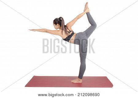young asian woman doing yoga in Natarajasana or Lord of the Dance yoga pose on the mat isolated on white background exercise fitness sport training and healthy lifestyle concept