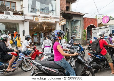 Ubud, Bali Indonesia - April 19, 2013 - People ride motorbikes at main commercial street of tourist centre Ubud in Central Bali region