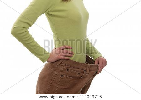 Teenager girl wearing several sizes too big trousers, holding it up with hand. Cut out, isolated on white.