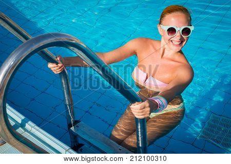 Young woman enjoying warm water in pool at tourist resort