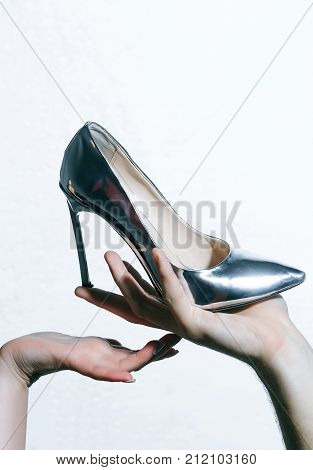 Shoe on high heel stiletto in hands isolated on white. Black friday cyber online shopping sale ecommerce. Presenting product promotion advertising. Fashion vogue style.