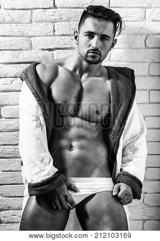 Handsome man or muscular macho bodybuilder with sexy muscle torso body with six packs and abs in sexi underpants and bathrobe poses on white brick wall