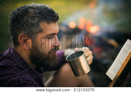 Man Traveler Read And Drink At Campfire Flame