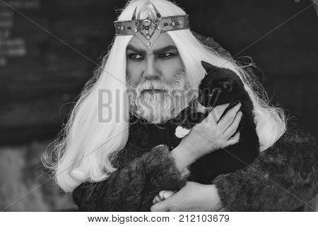Druid old man with long grey hair and beard with crown in fur coat holds cat on dark background