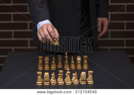 Businessman ponders a strategy of behavior on the market. Chess tournament. Carier start. Chess as an instrument of behavior. A man in a suit makes a move as a chess piece.