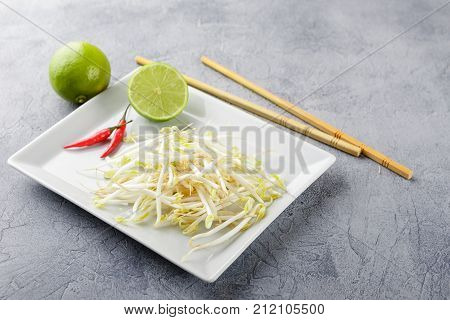 Fresh bean sprouts on white square plate and chopsticks. Concept of healthy foods vegetarian food.