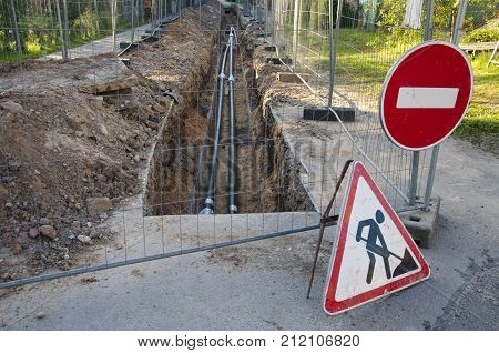Trench in street with black plastic heating water tube and road signs