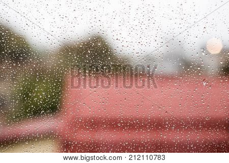 Raindrops On Window Glass With Cloudy Sky And City Roofs As Background