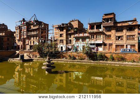 BHAKTAPUR NEPAL - NOVEMBER 15, 2016: Traditional nepalese newar houses near the green pond in Bhaktapur, Nepal.
