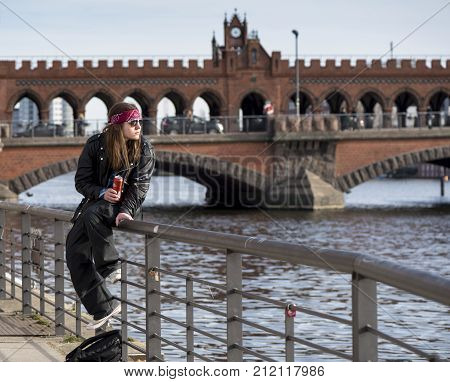 Berlin, Germany - March 2017: youngster at the river bank with Oberbaunbrucke Bridge at the background