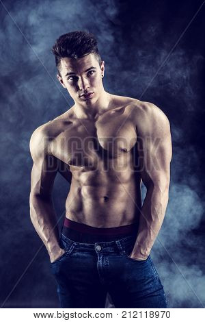 Handsome young muscular man shirtless wearing jeans, on dark background in studio shot