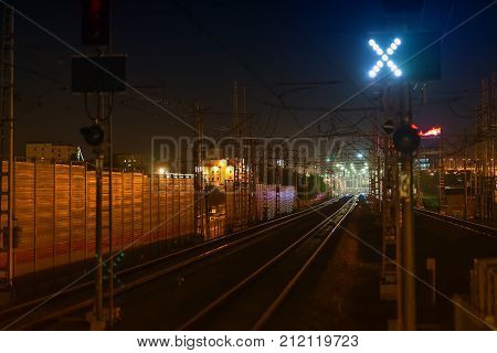 Railroad night scene with blue traffic light and railway station tracks night view golden tones and colors. Industrial transportations travel