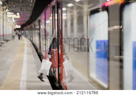 Railway subway station at night at dusk passenger train stopped. Unrecognizable girl enters the train. Passenger transportation style of life. Blurred background