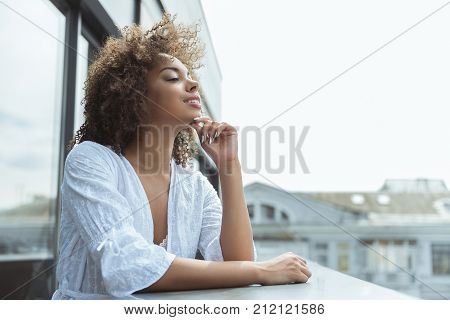 Side view happy mulatto girl looking from balcony. Copy space