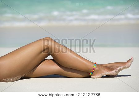 Beach Travel - Woman Seated On Sand Beach. Closeup Detail Of Female Feet