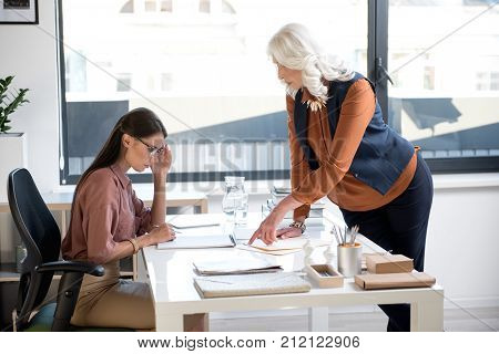 Look at this. Profile of upset young girl in glasses is sitting at table and touching her face. Confident senior elegant lady is leaning over desk and pointing on documents while expressing discontent