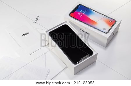 PARIS FRANCE - NOV 3 2017: Unboxing unpacking of the latest Apple iPhone X 10 smartphone on white table with accesories instruction manual