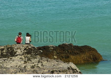 A young couple sepaking in front of the sea poster