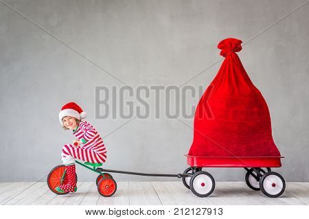 Happy child with Christmas gift. Kid having fun at home. Xmas holiday concept