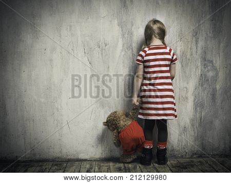 Sad girl with a toy bear standing back in the background of the textured walls. The concept of children's resentment the complexity of education the child's behavior