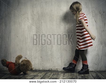 The wicked girl threw a toy bear. Background textured wall. The concept of children's resentment the complexity of education the child's behavior