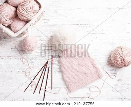 Pink coil of yarn in the basket and knitting needles. Handmade knitted pink hat with with fur pompom knitting accessories on a white wooden table.