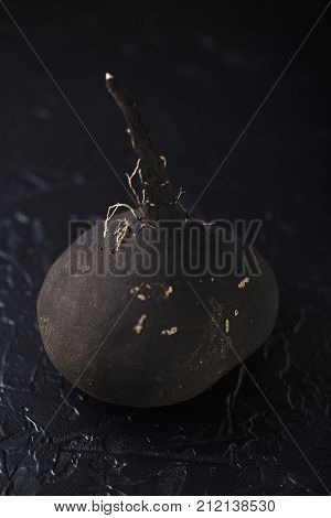 Tuber black radish on a black concrete background