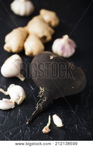 Tuber black radish and garlic on a black concrete background