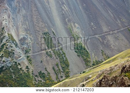 The old abandoned road along a steep hillside with rocky scree in the Tien Shan Kyrgyzstan Steep slopes precipices steep rocks in the inaccessible mountains.