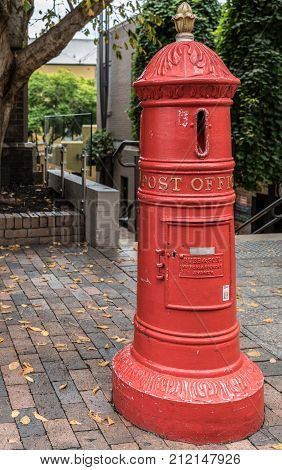 Sydney Australia - March 22 2017: Red historic street post office mail box in The Rocks neighborhood. Circular tool with vertical slit ton insert mail pieces. Sidewalk scenery with green vegetation.