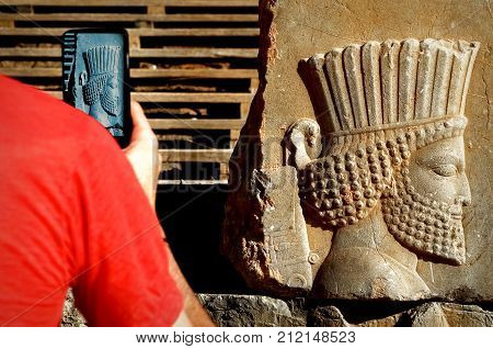Persepolis is the capital of the ancient Achaemenid kingdom. sight of Iran. Ancient Persia. Bas-relief carved on the walls of old buildings. The tourist makes photos of attractions on the smartphone.