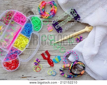 Colorful Of Elastic Rainbow Loom Bands Kit And Bracelets On Wooden Background
