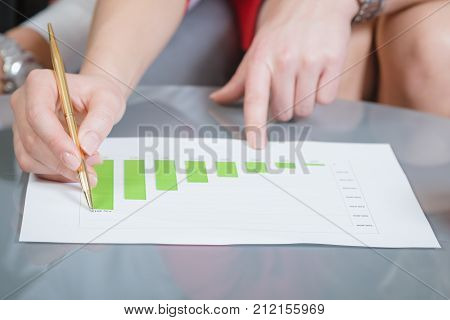 Close up of businesswoman showing financial chart