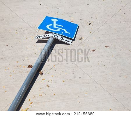 Reserved parking sign knocked over on the road. The letters in Hebrew read
