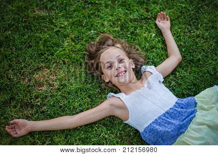 Smiling little girl lying on the grass with happy carefree expression - concept of freedom in childhood