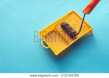 Roller For Paint And Painting Capacity On Blue Background Surface. Home Repair Creativity Concept